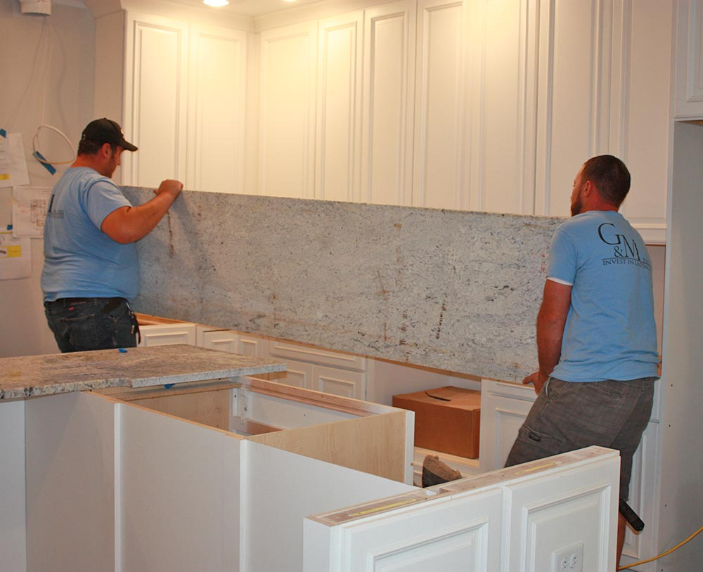 experts moving stone countertop in place for installation