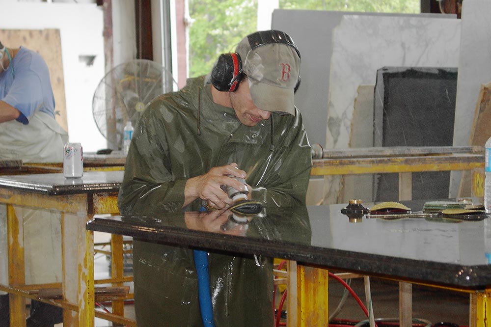 employee polishing stone for countertop in Saratoga factory